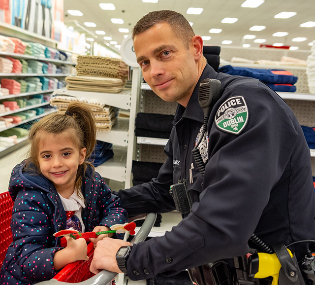 Officer pushes little girl in a shopping cart at a store during a holiday event.