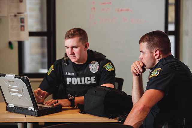 Two police officers study laptop together.